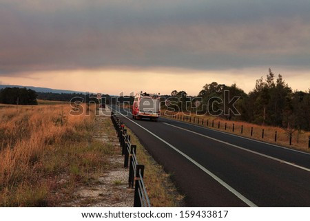 A  Rural Fire Service, fire and rescue vehicle responds urgently to a large out of control bushfire in the mountains.  Smoke and sun casts a red glow across landscape.  Thick smoke billowing overhead - stock photo