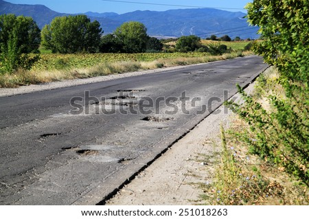 A rural road with lots of potholes. - stock photo