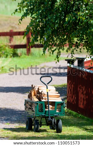 A rural scene with a small hand operated trolley loaded with a stockpile of sawn and split timber fetching in the wood for heating the stove and house - stock photo