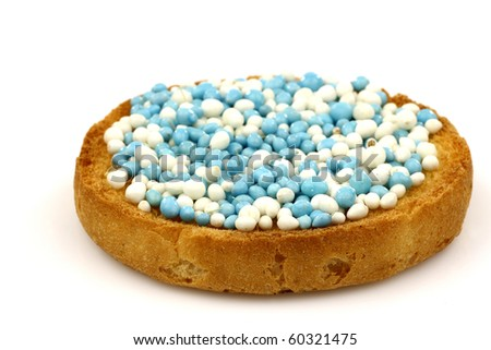 a rusk with blue and white anise seed sprinkles served in Holland when a baby boy is born on a white background - stock photo