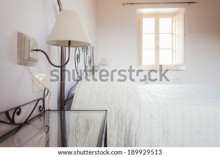 a rustic double  bed in a luminous bed room - stock photo