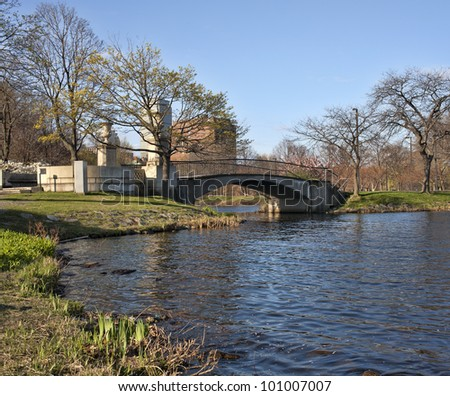 A rustic footbridge over water with trees and city in the background. - stock photo
