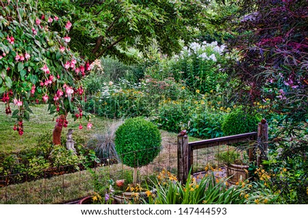 A rustic gate flanked by two round hedge bushes leads into a tranquil country garden done in a nostalgic illustrative style. - stock photo