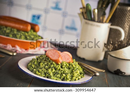 A rustic kitchen with a plate with 'Boerenkool met worst' or kale with smoked sausage, a traditional Dutch meal. Served with gravy. With typical Dutch Delft blue tiles on the wall in the background. - stock photo