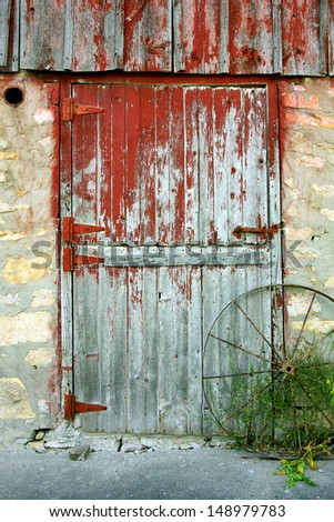 a rustic old barn door with peeling red paint, stone walls, and an antique wagon wheel - stock photo