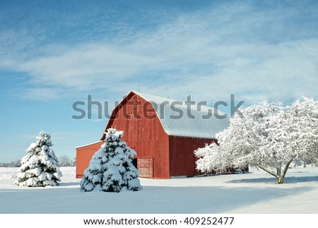 A rustic red barn in Ohio covered in fresh snow with a bright blue sky background. - stock photo