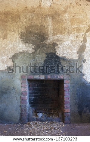 A rustic, well used, brick fireplace set in an old, crumbling wall. - stock photo