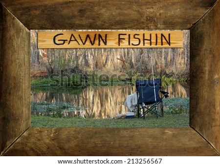 "A rustic wood picture frame surrounds a photo of the author's favorite fishing hole and an engraved wood sign that reads, ""GAWN FISHIN."" - stock photo"
