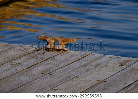 A rusting pier tie down hangs loosely at the edge of a wooden dock at dusk - stock photo