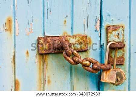 A rusty chain on a weathered wooden door with a padlock - stock photo