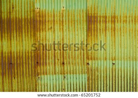 A rusty corrugated iron metal fence close up/ Zinc wall - stock photo