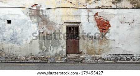 A rusty metal old backdoor on a dilapidated grungy brick wall in a back alley.   - stock photo