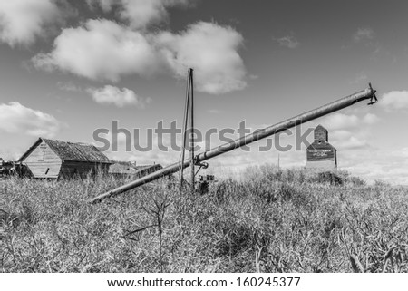 A rusty old grain auger in an old ghost town - stock photo