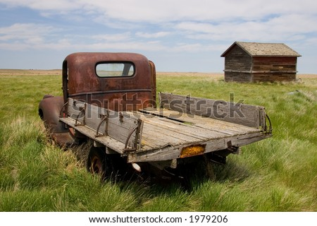 A rusty old pickup truck and shed in a field - stock photo