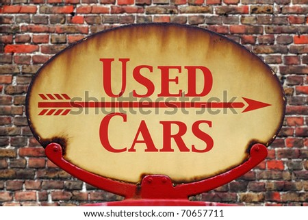 A rusty old retro arrow sign with the text Used cars - stock photo