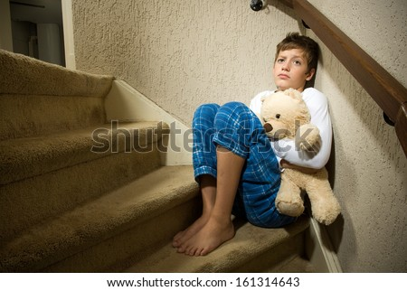 A sad and depressed boy is sitting in the corner of a staircase - stock photo