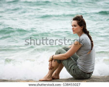 A sad and pensive woman sitting by the ocean deep in thought. - stock photo