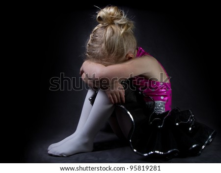 A sad dancer in a spotlight on a black background - stock photo
