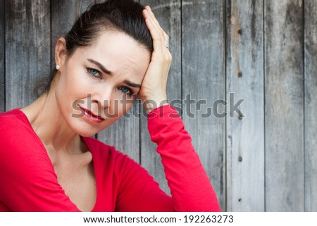 A sad, depressed and lonely woman sitting by a wooden wall or door. - stock photo