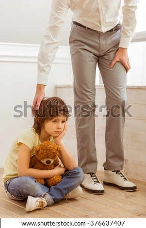 A sad little boy hugging a teddy bear while sitting on the floor. A father holding hand on his son's head. - stock photo