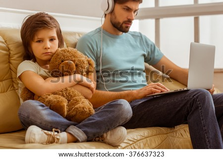 A sad little boy looking in camera and hugging a teddy bear while his father using a laptop - stock photo