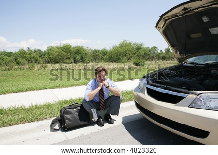 A sad looking businessman sitting on the curb waiting for the motor club. - stock photo