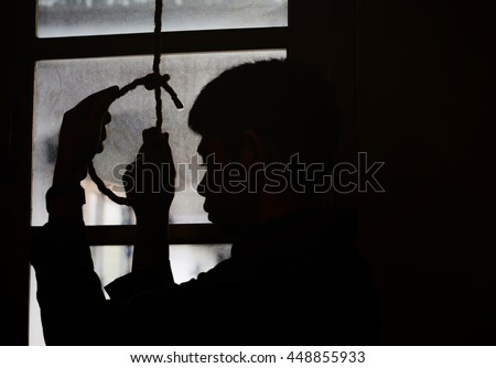 a sad man holding hangman noose in the dark room  against the window while  making decision  to suicide - stock photo