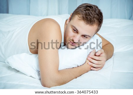 A sad Man lying on the bed, head resting upon pillow - stock photo