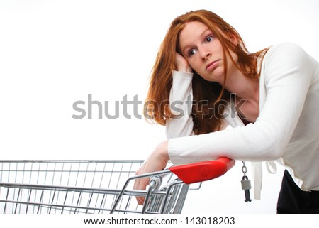 A sad shopping girl leaning on her empty shopping cart. - stock photo