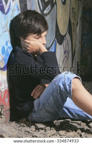 A sad teen sit on the ground of a graffiti wall - stock photo
