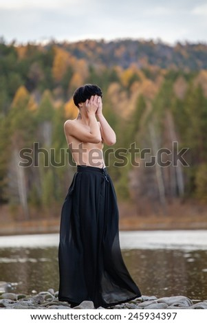 A sad woman wearing black standing on the bank of a river. - stock photo