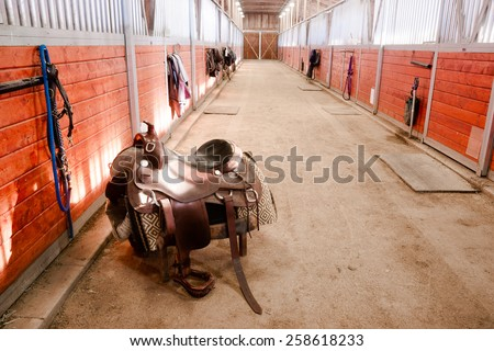 A saddle waits to be mounted on horses back at stables - stock photo