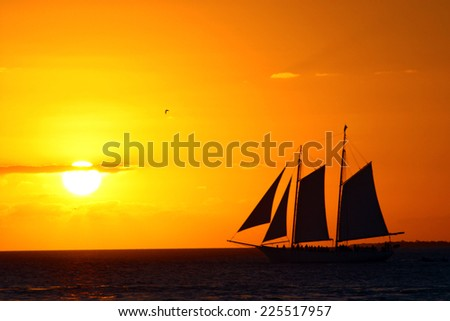 A sail boat against a sky lit in shades of yellow and orange. - stock photo