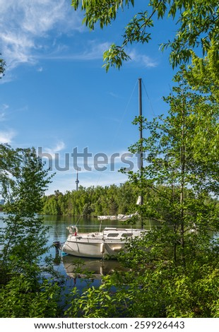 A sail boat anchored on the waters edge is partially hidden by trees on Centre Island in Toronto Canada. - stock photo