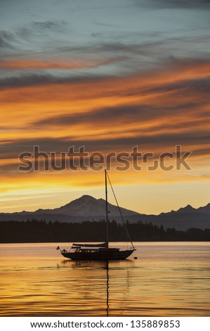 A sailboat anchors off of Lummi island, located in the San Juan Islands of the Puget Sound area of western Washington state. The volcano,Mt. Baker, can be seen in the background. - stock photo
