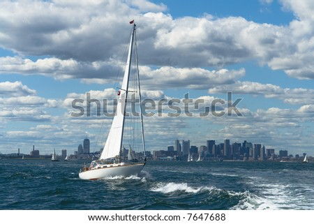 A sailboat crosses wake in front of Boston - stock photo
