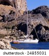 A sailboat moored by a small cove just outside of Lindos on the Greek island of Rhodes - stock photo