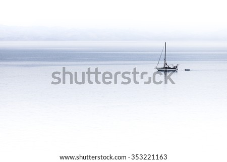 A sailboat navigating with calm and peace alone in the ocean - stock photo