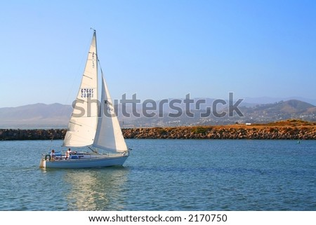 A sailboat on a sunny day with clear blue skies. - stock photo