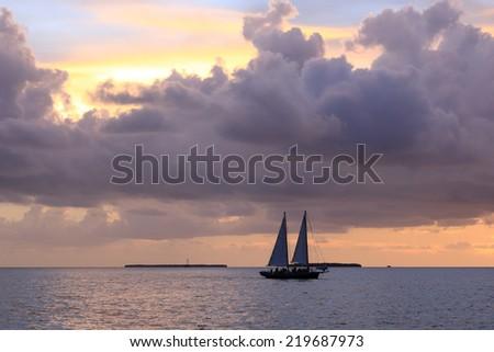 A sailboat plies a calm sea at sunset. - stock photo
