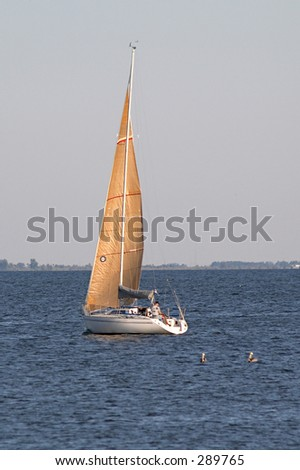 A sailboat with golden sails. - stock photo