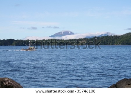 A salmon fishing boat passes in front of Sitka Alaska's Mt. Edgecumbe volcano - stock photo