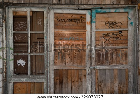 A sample of ubiquitous Greek grafitti on old wooden doorway. - stock photo