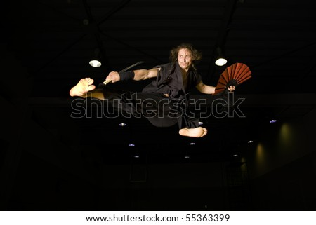 a samurai warrior flying high in an action kick - stock photo