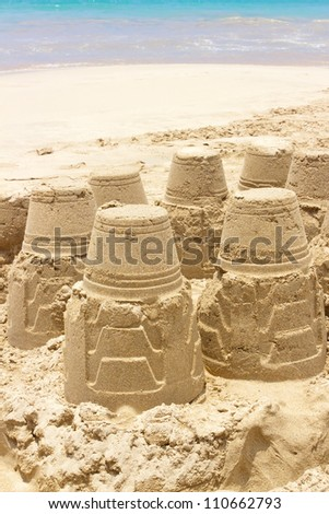 A sand castle at the beach against crystal blue water - stock photo