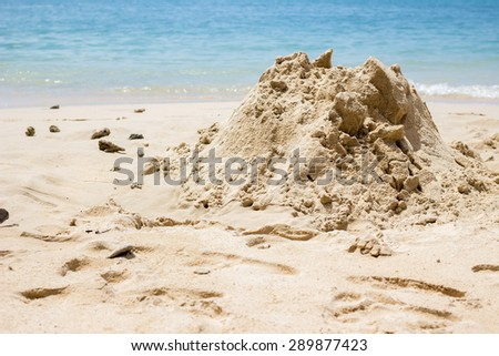 A sand pile prepare to be castle at the beach against crystal blue water - stock photo