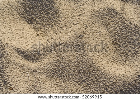 A sandy background with some visual interest through the divots and peaks in it. - stock photo