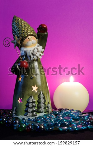 A Santa Claus candle holder and a burning spherical candle with blue glass stones against a magenta background - stock photo