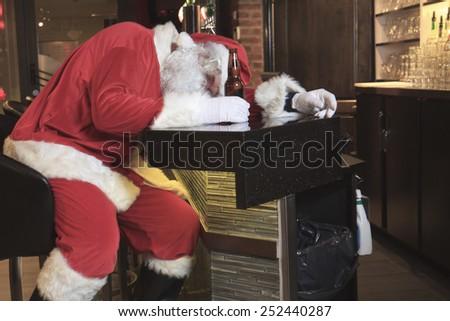 A Santa claus sleep at the bar. Too drunk. - stock photo