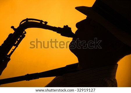 A saxophone player with a hat in silhouette against a stage light gold or yellow background in the horizontal format with copy space. - stock photo